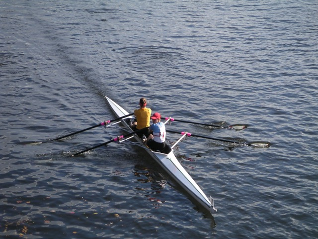 2 persons in rowing shell on water