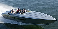 A fast High Performance boat with several people in it, traveling at swift speed accross the water